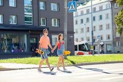 Pares adolescentes con los monopatines en la calle de la ciudad Fotos de archivo libres de regalías