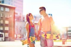Pares adolescentes con los monopatines en la calle de la ciudad Imagen de archivo libre de regalías
