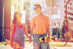 Pares adolescentes con los monopatines en la calle de la ciudad Imagenes de archivo