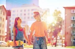 Pares adolescentes con los monopatines en la calle de la ciudad Imagen de archivo