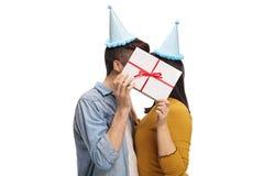 Pares adolescentes con los sombreros del partido que se besan detrás de un presente Imagen de archivo