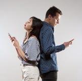 Pares adolescentes con mandar un SMS de los smartphones Imagenes de archivo