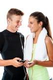 Pares adolescentes de la aptitud con los teléfonos elegantes Imagen de archivo libre de regalías
