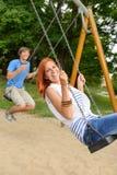 Pares adolescentes de risa en el oscilación en parque Fotografía de archivo libre de regalías