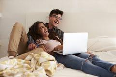 Pares adolescentes de risa que cuelgan hacia fuera en dormitorio usando el ordenador portátil Fotografía de archivo libre de regalías
