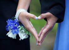 Pares adolescentes del baile de fin de curso que forman el corazón de la mano entre ellos Fotos de archivo libres de regalías