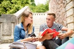 Pares adolescentes del estudiante delante de estudiar de la universidad Imagenes de archivo