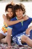 Pares adolescentes del retrato en la playa Imagen de archivo libre de regalías
