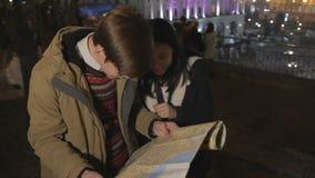 Pares adolescentes dulces que ríen y que buscan la ubicación en mapa de la ciudad, turismo almacen de video