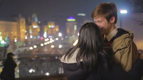 Pares adolescentes emocionados en el amor que disfruta de la fecha romántica en ciudad hermosa de la noche almacen de metraje de vídeo