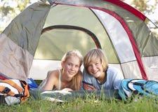 Pares adolescentes en acampada en campo Imágenes de archivo libres de regalías