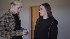 Pares adolescentes en casa junto La mujer joven da la prueba de embarazo para servir, él la lanza lejos y sale del cuarto almacen de video