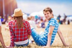 Pares adolescentes en el festival de música del verano, sentándose delante de sta Imagen de archivo