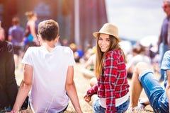 Pares adolescentes en el festival de música del verano, sentándose delante de sta Imagen de archivo libre de regalías