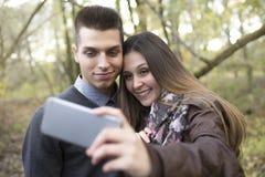 Pares adolescentes en el parque del otoño Foto de archivo