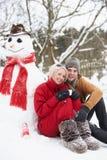 Pares adolescentes en paisaje del invierno al lado del muñeco de nieve Fotos de archivo
