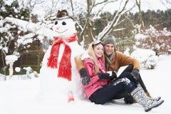 Pares adolescentes en paisaje del invierno al lado del muñeco de nieve Fotografía de archivo libre de regalías