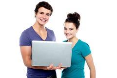 Pares adolescentes encantadores que sostienen una computadora portátil Imágenes de archivo libres de regalías