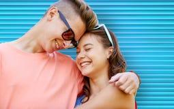 Pares adolescentes felices con el abrazo de las gafas de sol Fotografía de archivo