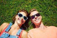 Pares adolescentes felices con los auriculares que mienten en hierba Imágenes de archivo libres de regalías