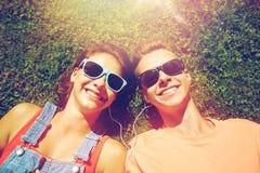 Pares adolescentes felices con los auriculares que mienten en hierba Imagenes de archivo