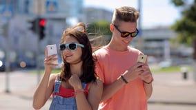 Pares adolescentes felices con smartphones en ciudad almacen de video