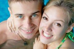 Pares adolescentes felices en la piscina Imágenes de archivo libres de regalías