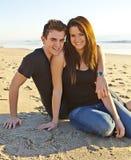 Pares adolescentes felices en la playa Foto de archivo