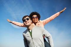 Pares adolescentes felices en las sombras que se divierten al aire libre Imagen de archivo
