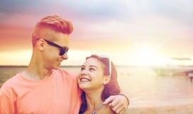 Pares adolescentes felices que abrazan en la playa del verano Foto de archivo