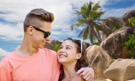 Pares adolescentes felices que abrazan en la playa del verano Foto de archivo libre de regalías
