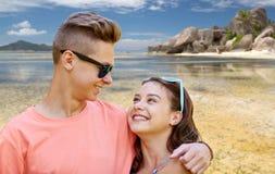 Pares adolescentes felices que abrazan en la playa del verano Fotografía de archivo libre de regalías