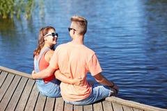 Pares adolescentes felices que abrazan en litera del río Foto de archivo libre de regalías