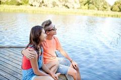 Pares adolescentes felices que abrazan en litera del río Fotos de archivo libres de regalías