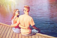 Pares adolescentes felices que abrazan en litera del río Imagen de archivo