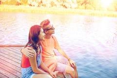 Pares adolescentes felices que abrazan en litera del río Fotos de archivo