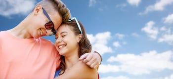 Pares adolescentes felices que abrazan sobre el cielo azul Fotos de archivo