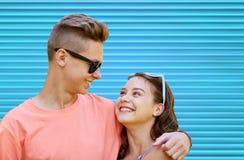 Pares adolescentes felices que abrazan sobre fondo azul Imagen de archivo libre de regalías