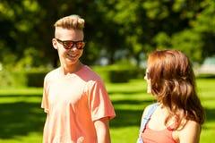 Pares adolescentes felices que caminan en el parque del verano Fotos de archivo libres de regalías