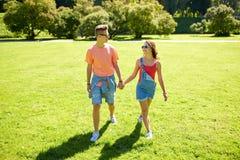 Pares adolescentes felices que caminan en el parque del verano Imagen de archivo libre de regalías