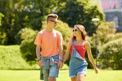 Pares adolescentes felices que caminan en el parque del verano Imágenes de archivo libres de regalías