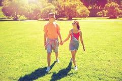 Pares adolescentes felices que caminan en el parque del verano Foto de archivo