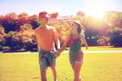 Pares adolescentes felices que caminan en el parque del verano Fotografía de archivo