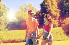 Pares adolescentes felices que caminan en el parque del verano Fotos de archivo