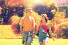Pares adolescentes felices que caminan en el parque del verano Foto de archivo libre de regalías