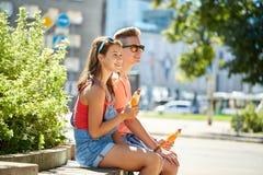 Pares adolescentes felices que comen los perritos calientes en ciudad Foto de archivo