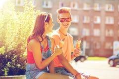 Pares adolescentes felices que comen los perritos calientes en ciudad Imagenes de archivo