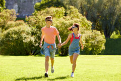 Pares adolescentes felices que corren en el parque del verano Fotos de archivo