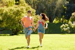 Pares adolescentes felices que corren en el parque del verano Foto de archivo