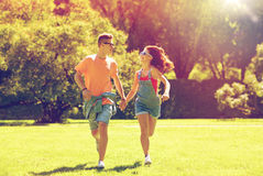 Pares adolescentes felices que corren en el parque del verano Imágenes de archivo libres de regalías